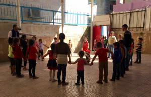 Kids playing at the Youth Club of the Refugee Camp. They are standing in a circle, holding their hands.